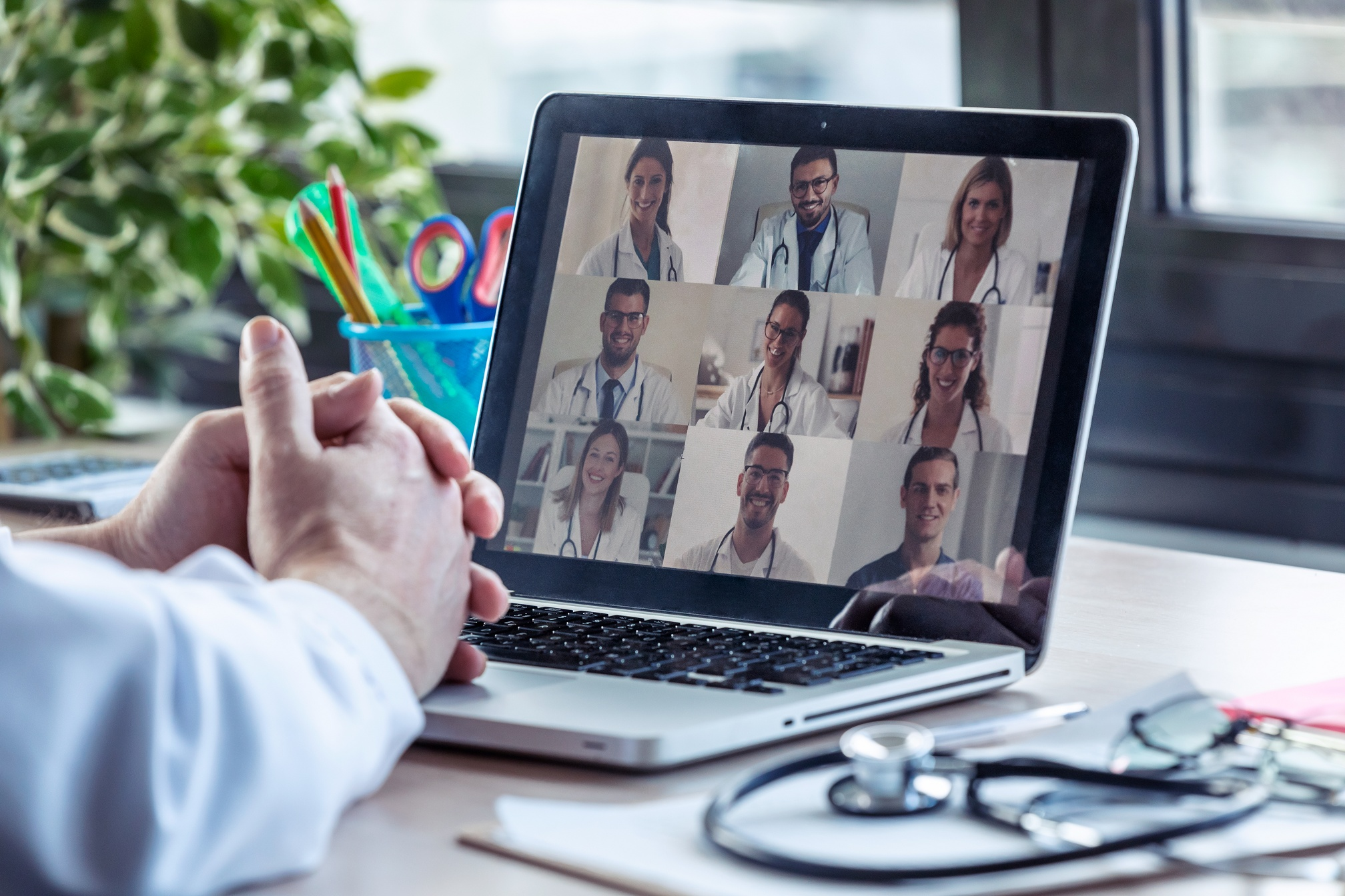 Male doctor having video conference on laptop with his colleague